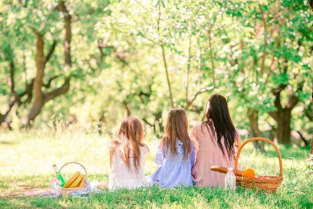 La madre felice e le piccole figlie si rilassano sul lago