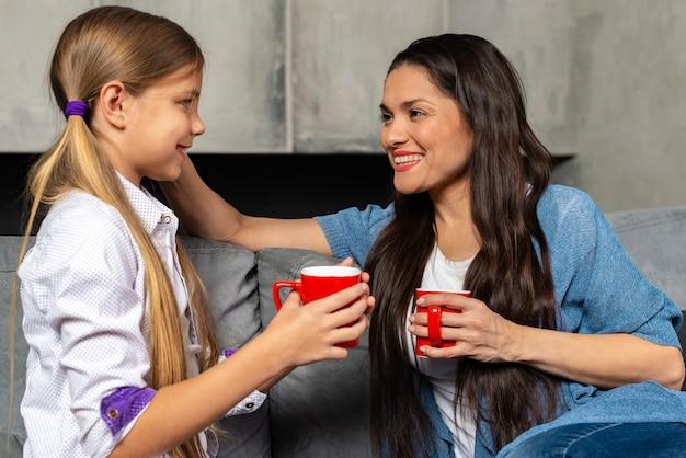 La madre felice e sua figlia stanno parlando mentre si sedevano sul letto
