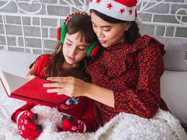 La madre ha letto un libro a sua figlia il giorno di natale, concetto