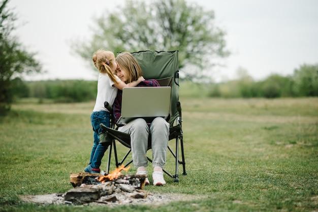 La madre lavora su internet con il bambino all'aperto. comunicazione con la famiglia in linea sul computer portatile vicino al fuoco in natura. homeschooling, lavoro freelance.