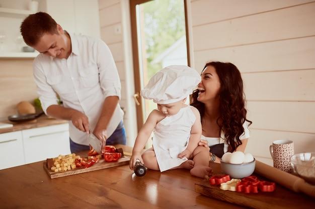 La madre, padre e figlio seduti in cucina