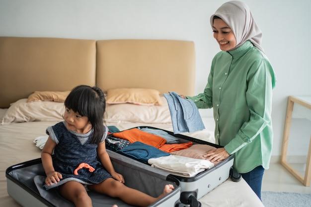 La madre prepara i vestiti e sua figlia gioca con la sua valigia