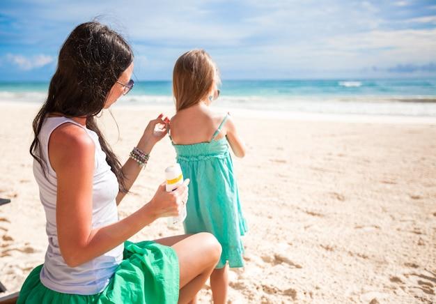 La madre protegge il suo bambino dal sole con la crema solare