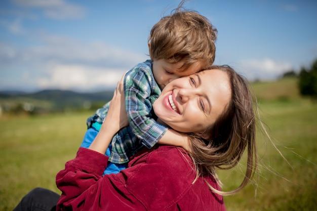 La madre si diverte con un figlio su un prato in montagna