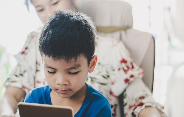 La madre sta guidando suo figlio a usare il tablet nel modo giusto
