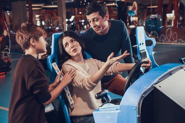 La madre sta guidando un'auto in arcade. la famiglia la sta confortando.