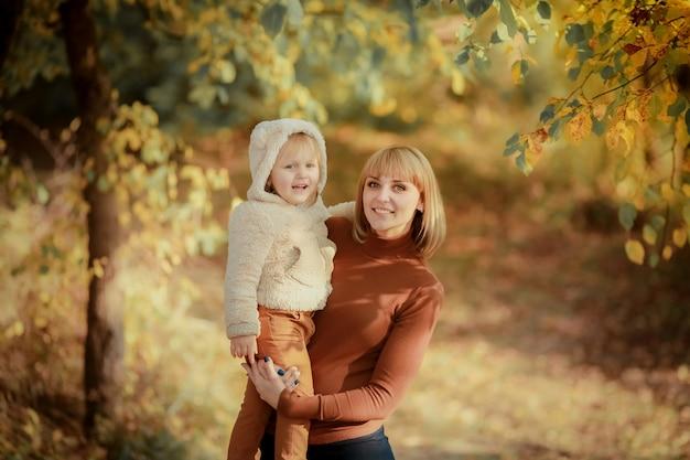 La madre tiene la figlia di 3 anni nelle mani di e va tra le foreste di fogliame giallo