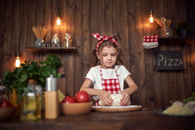 La maglietta bianca d'uso sorridente della ragazza con il grembiule a quadretti e la fascia che impasta la pasta di pane sulla tavola ha riempito di ingredienti per pizza in cucina di legno alla moda.