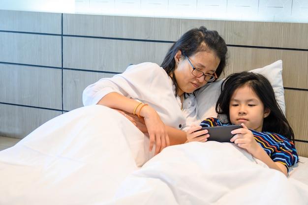 La mamma asiatica e sua figlia stanno usando uno smartphone e stanno sorridendo sul letto a casa
