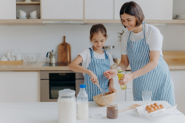 La mamma bruna aggiunge olio nell'impasto, la piccola figlia aiuta a fare la pasta, sbatte gli ingredienti
