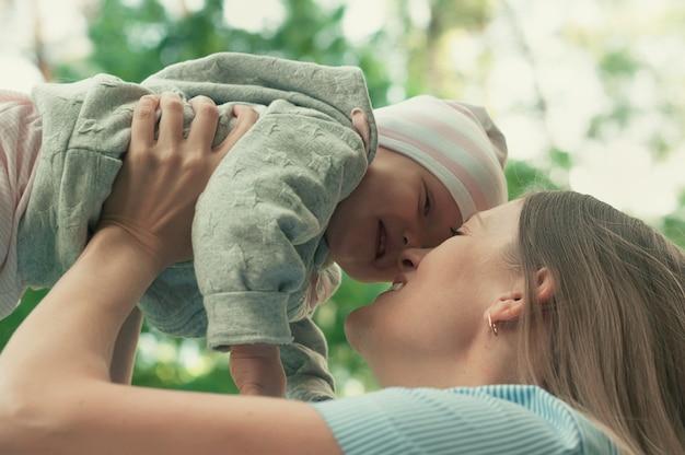 La mamma cammina con il bambino nel parco. il bambino tra le sue braccia. primavera.