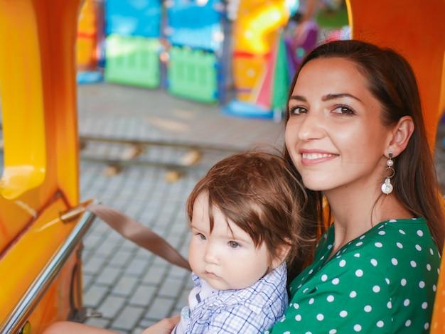 La mamma cavalca un treno per bambini con un bambino. la mamma cavalca con un bambino su una giostra. ritratto di una madre e un figlio felici cavalcando una giostra