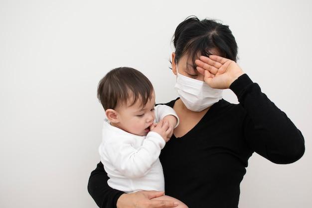 La mamma che è malata di raffreddore e influenza porta suo figlio in braccio