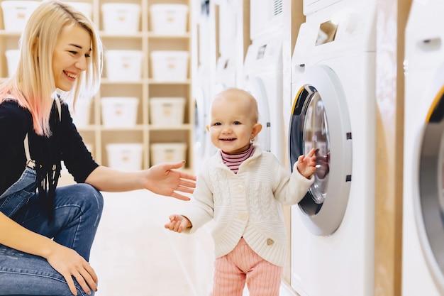 La mamma e il bambino in lavanderia prendono le cose e giocano