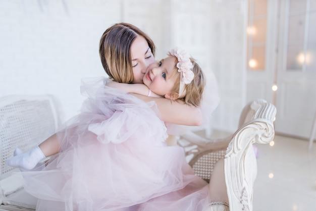 La mamma e la figlia adorabili si abbracciano tenero che si siede sulla sedia bianca