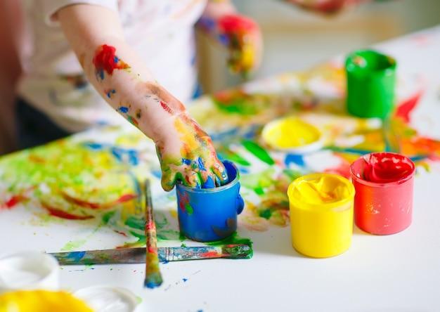 La mamma e la figlia dipingono su tela alla scuola di disegno