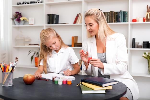 La mamma e la figlia felici e sorridenti che si siedono alla tavola e che disegnano dipingono insieme
