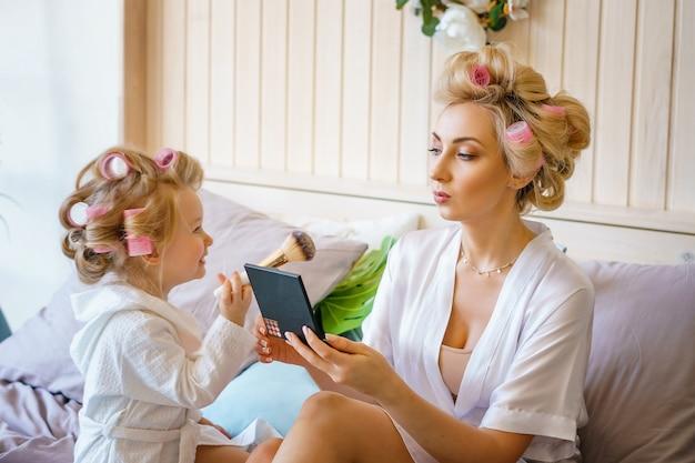 La mamma e la figlia felici fanno un trucco che si siede sul letto nella camera da letto