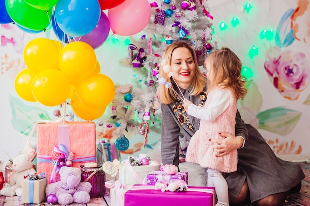 La mamma e la figlia giocano prima di un albero di natale nella stanza rosa