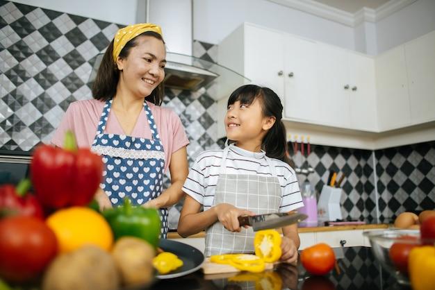 La mamma e sua figlia si aiutano a preparare la cucina in cucina a casa.