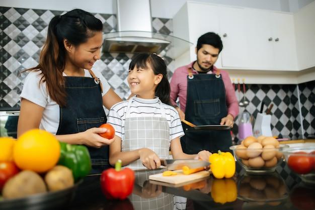 La mamma felice insegna alla figlia a tagliare gli ingredienti per la preparazione delle verdure