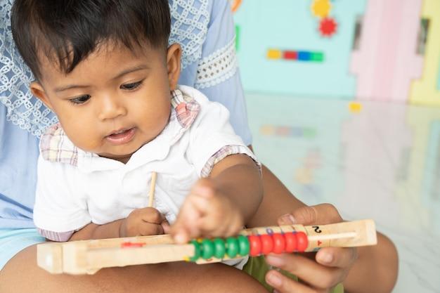 La mamma gioca al giocattolo di legno con il neonato
