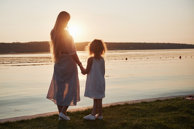 La mamma gioca con il suo bambino in vacanza vicino all'oceano, sagome al tramonto