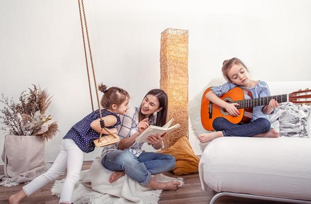 La mamma gioca con le sue figlie a casa. lezioni su uno strumento musicale, chitarra. il concetto di amicizia e famiglia dei bambini.