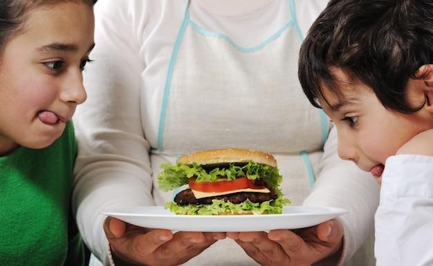 La mamma ha preparato deliziosi hamburger per ragazzino e ragazza