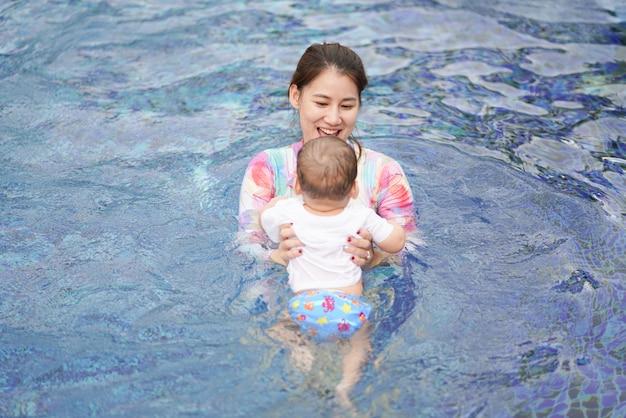 La mamma insegna a un bambino a nuotare in piscina così felice e divertente