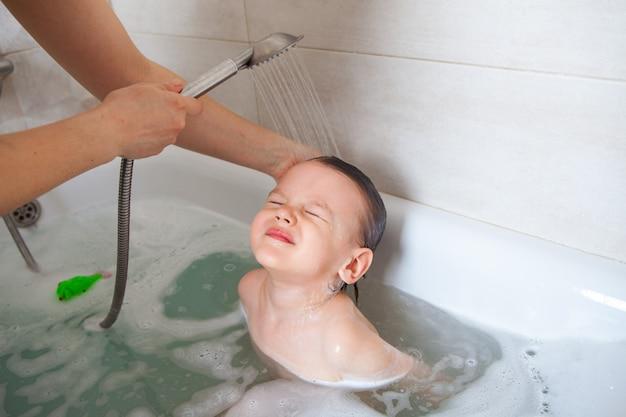 La mamma lava la testa del suo bambino in un bagno con acqua. schiuma shampoo doccia a filo.