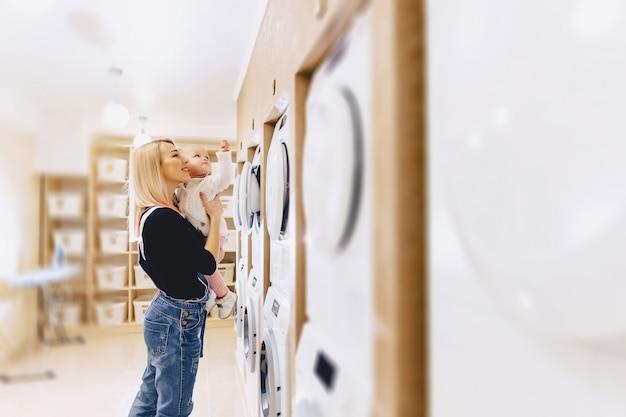 La mamma mostra a sua figlia una lavatrice