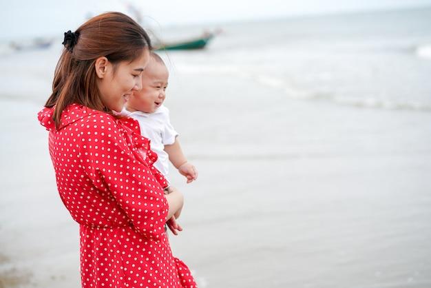 La mamma porta il bambino sulla spiaggia così felice