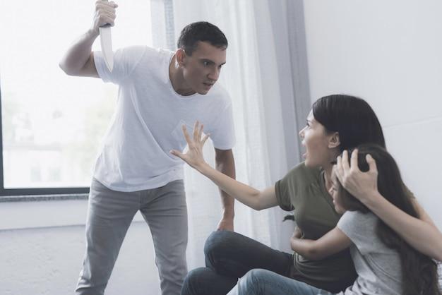 La mamma protegge la ragazza dal papà minaccioso con il coltello