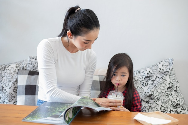 La mamma sta alzando un bicchiere di latte freddo, la figlia beve e insegna a sua figlia a leggere un libro.