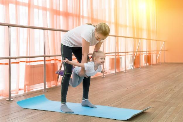 La mamma tiene in braccio una figlia che si esercita in ginnastica.