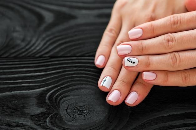 La manicure, rosa con colore bianco, isolato su uno sfondo di legno nero