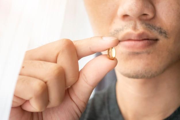 La mano alta vicina sta tenendo le pillole delle vitamine