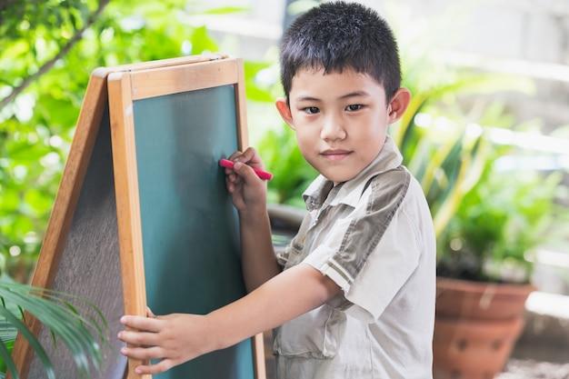 La mano asiatica dei punti del ragazzino scrive sulla lavagna
