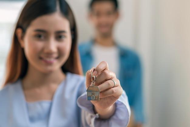 La mano asiatica della giovane donna del primo piano che tiene la catena chiave della casa sopra la foto ha offuscato