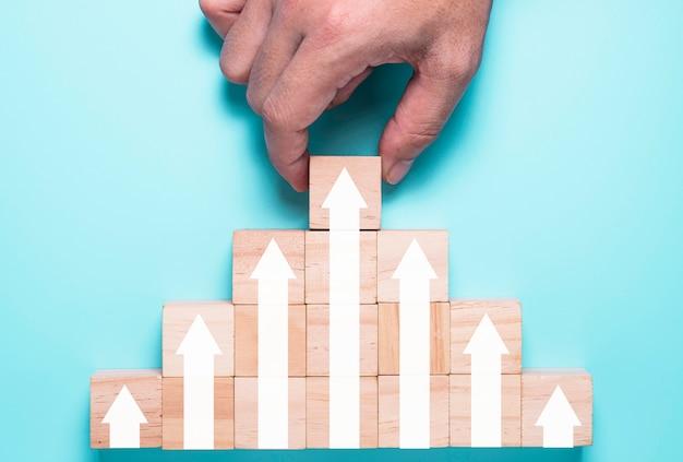 La mano che mette i cubi di legno blocca quale aumento dello schermo di stampa o freccia bianca in alto. è il simbolo della crescita dei profitti degli investimenti economici.