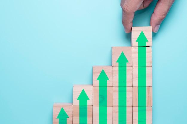 La mano che mette i cubi di legno blocca quale aumento dello schermo di stampa o freccia verde in alto. è il simbolo della crescita dei profitti degli investimenti economici.