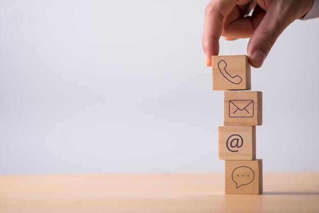 La mano che mette l'icona del contatto commerciale include il numero di telefono indirizzo e-mail e messaggi che stampano lo schermo sul cubo di legno.