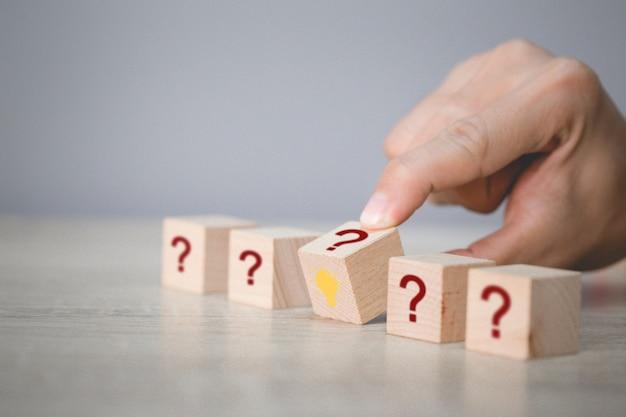 La mano che organizza lancia l'impilamento del blocco di legno con il punto interrogativo e la lampada dell'icona, pensando con il concetto del punto interrogativo.