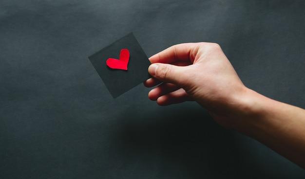 La mano che regge un cuore nero su sfondo nero, san valentino. flat lay