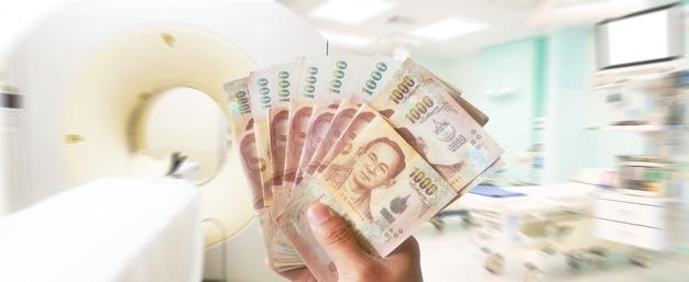 La mano che tiene i soldi di baht tailandesi gioca per il concetto medico, finanziario e medico.