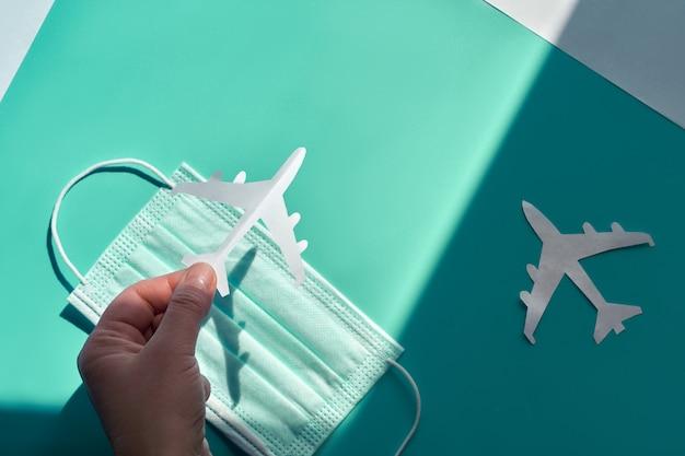 La mano che tiene l'aereo di carta sopra la maschera facciale lo prende dall'ombra alla luce. il viaggio aereo riprende dopo il viaggio. le vacanze si fermarono e i confini si chiusero durante le pandemie di coronavirus. confini aperti, fine della quarantena.