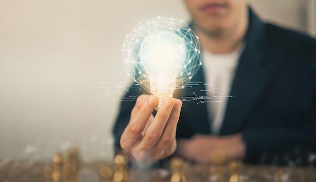 La mano che tiene la lampadina con innovazione e creatività sono le chiavi del successo.