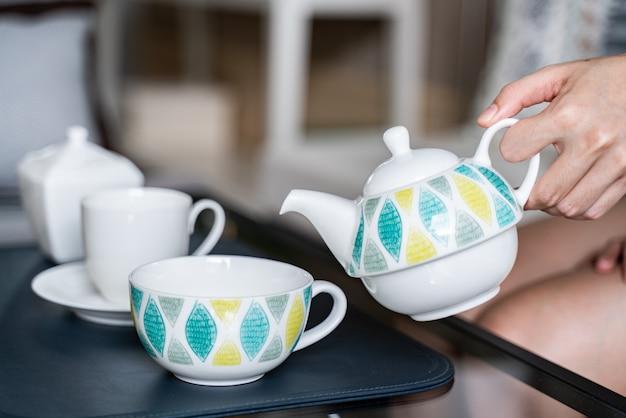 La mano che tiene la pentola versa il tè in una tazza.