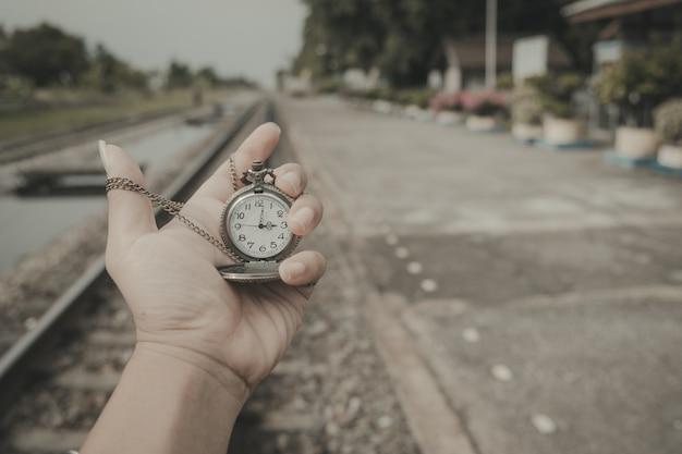 La mano che tiene un orologio sui binari riflette un viaggio che non finisce mai in stile vintage.